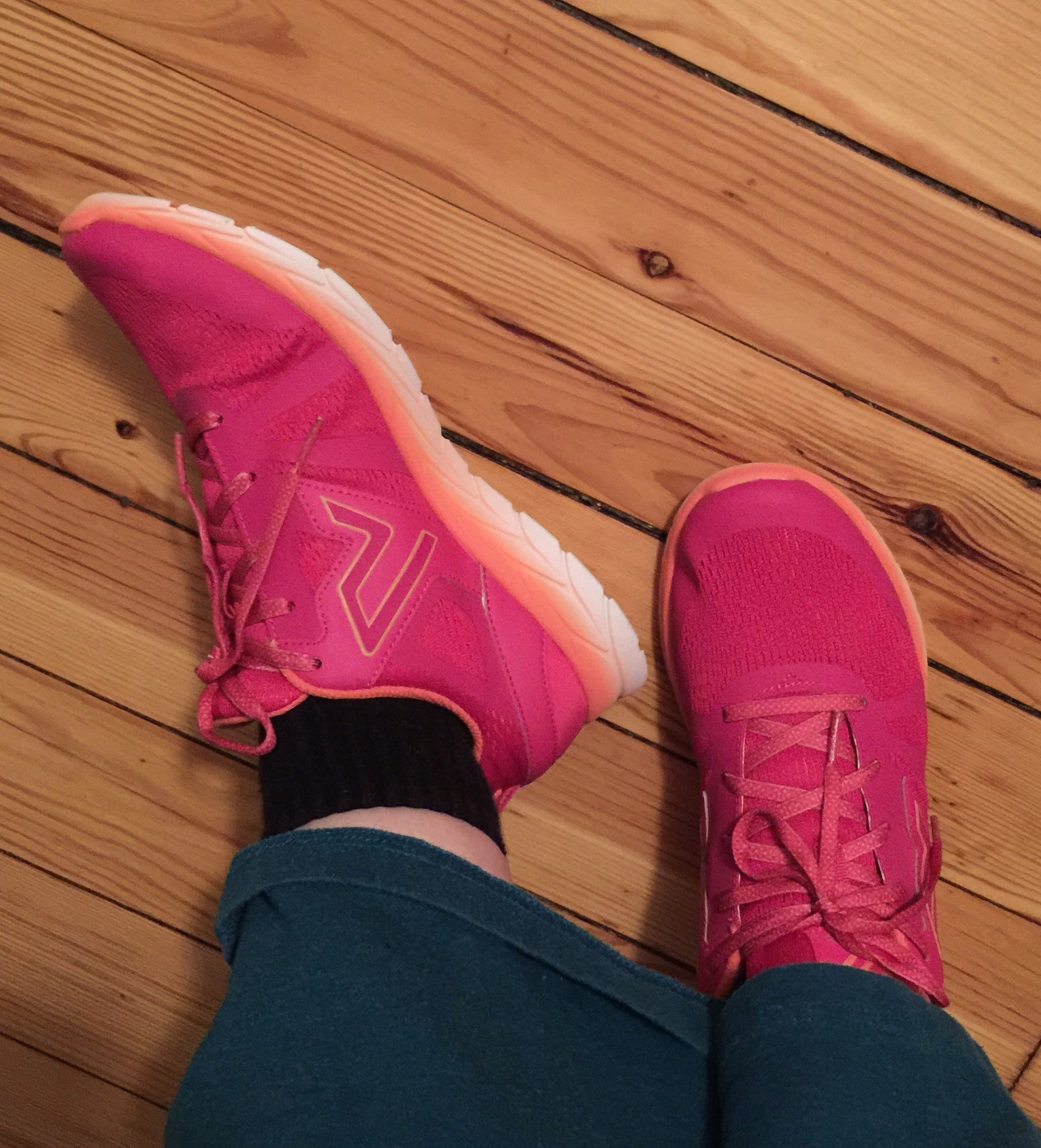 Bright pink sneakers with orange along the bottom edge and top of cuffs.